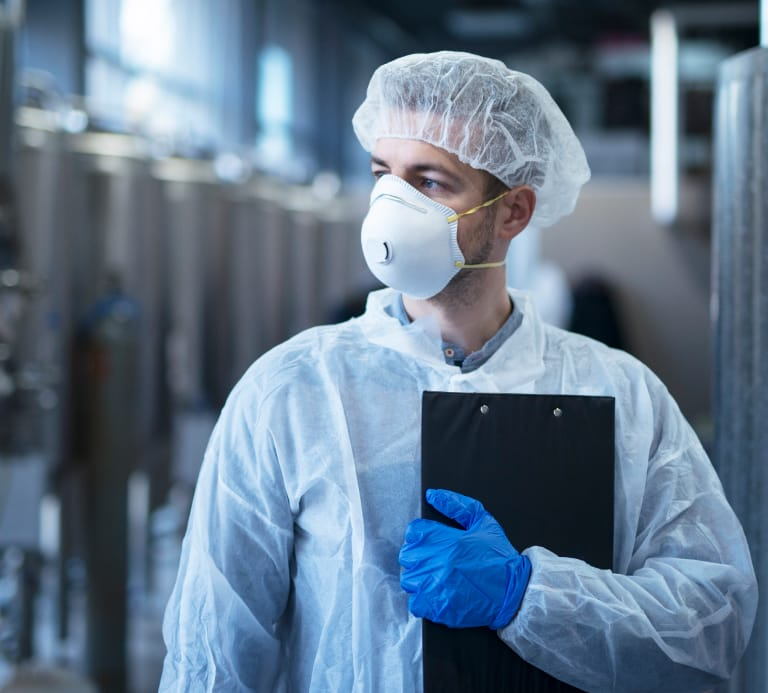 Man with clip board wearing white lab coat and face mask