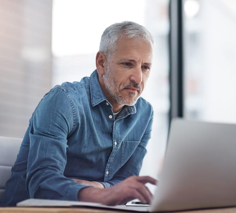 Man sat looking at a laptop