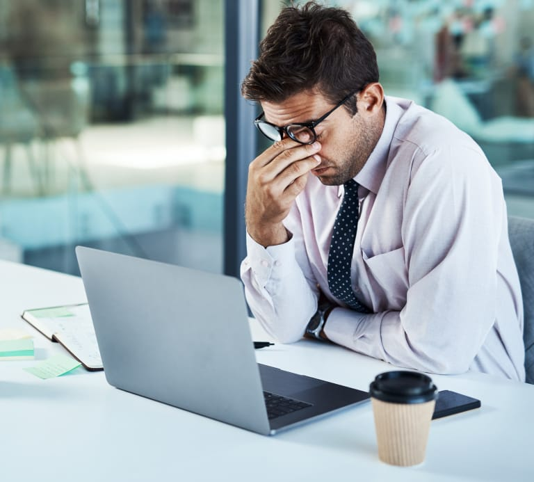 Photo of a man sat at his laptop looking stressed