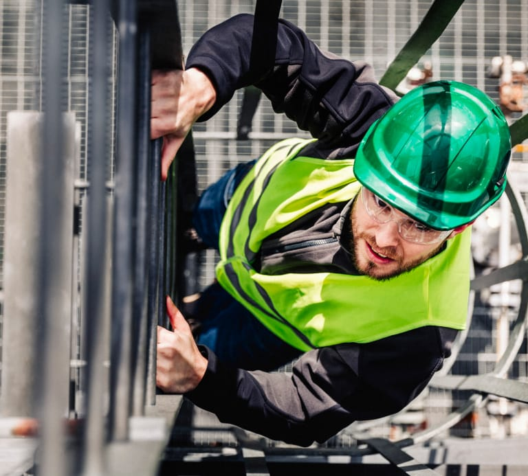 Photo of a man sat up a ladder wearing safety equipment